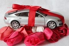 Valuable present for someone special concept. Luxury car tied up with a red ribbon with a bow on the roof as a gift on bright roses heads Royalty Free Stock Photo