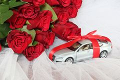 Valuable present for someone special concept. Wedding background. Luxury car tied up with a red ribbon with a bow on the roof as a gift and a bouquet of red Royalty Free Stock Photography