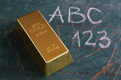 Value of Education Concept Gold Ingot on Old Schoolboard Stock Photos