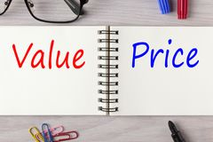 Value and Price written on notebook. Value and Price written in notebook on wooden desk with marker pen and glasses. Top view Royalty Free Stock Photography