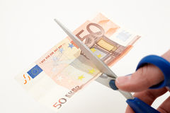 Valueless. Caucasian hand cutting a banknote with scissors Royalty Free Stock Images