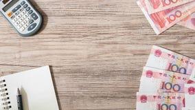Valuta cinese delle banconote di yuan e calcolatore, taccuino, matita su fondo di legno Immagini Stock