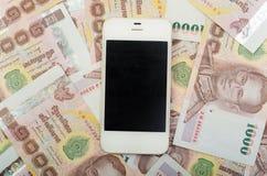 Valuta della Tailandia, baht tailandese 1000 con il cellulare. Immagini Stock