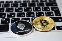 Valuta för faktiska Ethereum och Bitcoin mynt finansierar pengar på datorbärbar datortangentbordet Affär reklamfilm, utbyte arkivbilder