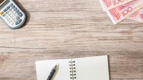 Valuta för kinesYuan sedlar och räknemaskin, anteckningsbok, blyertspenna på träbakgrund Fotografering för Bildbyråer