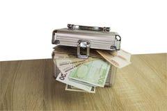 Valuta i en ask på en bakgrund för skrivbordisolatvit Arkivfoto