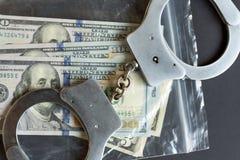 Valuta i en plast- packe och handbojor royaltyfri foto