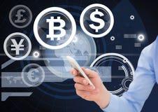 Valuta och biten myntar symboler och räcker innehavtelefonen arkivbild