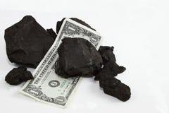 Valuta och kolstora bitar Arkivfoto