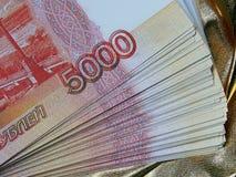 Valuta russa per 5000 rubli su un fondo dell'oro Fotografie Stock
