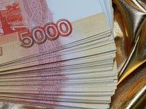 Valuta russa per 5000 rubli su un fondo dell'oro Immagini Stock