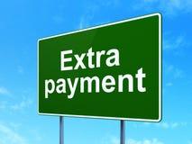 Valutabegrepp: Extra betalning på vägmärkebakgrund royaltyfria bilder