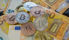 ValutaBitcoin BTC mynt på räkningar av eurosedlar worldwide Arkivbild