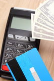 Valutadollar med kreditkorten och betalningterminal i bakgrund, finansbegrepp Arkivbild