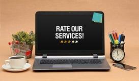 Valuti i nostri servizi firmano con le stelle sul monitor del computer portatile fotografia stock libera da diritti