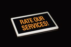 Valuti i nostri servizi per firmare, wrritten sullo schermo della compressa immagini stock libere da diritti