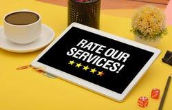 Valuti le nostre stelle di servizi con la tazza e la compressa di caffè fotografia stock libera da diritti