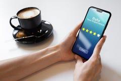 Valuti le vostre stelle di esame cinque di soddisfazione del cliente di esperienza sullo schermo del telefono cellulare Concetto  immagine stock