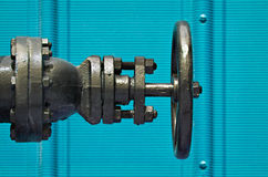 Valve. Black valve against a blue corrugated wall royalty free stock images
