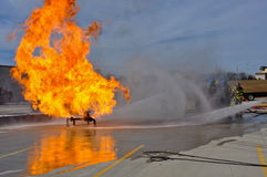 Valve on Fire. Gas valve on fire and firemen extinguishing the flames Stock Photos