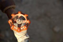 Valve Handle. Orange valve handle with brass plumbing Royalty Free Stock Photography