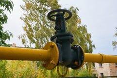 Valve noire sur le tuyau de gaz peint en jaune images libres de droits