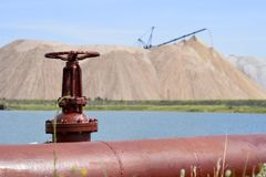 The valve from the pipeline against the background of a salt mine and artificial lake Stock Photo