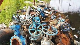 Valves de déchets abandonnées et rivière de pollution Photo stock