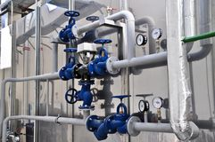 Valves in a factory where the pressure system is controlled. Blue valves controlling the pressure system royalty free stock photos