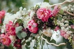 Valvgång av många beautifilblommor som gifta sig bågen med peones ceremoni arkivbilder