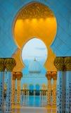 Valvgångar och kupol för storslagen moské guld- på skymning Royaltyfri Foto