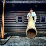 Vama, Romania, il 27 gennaio 2018: La ritrattistica di un uso dell'uomo tradizionale dal corno lungo ha chiamato il bucium Fotografia Stock Libera da Diritti