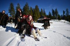Vama, Rumänien, am 20. Januar 2017: Kinder, die das traditionelle Kostüm spielt mit Pferdeschlitten auf hohem Schnee tragen Stockbilder