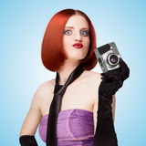 Vamp and glamour. Glamorous girl, retro vamp style, dressed in a necktie and long gloves, showing emotions and holding an old vintage photo camera on blue Stock Image