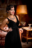 Vamp lady with red lips in restaurant. Vamp lady in black dress posing with her hand on hip. Beautiful woman with red lips looking at camera and holding glass of Stock Photography
