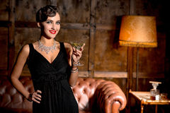 Vamp lady with red lips in restaurant. Vamp lady with red lips posing with glass of cocktail in restaurant. Elegant rich lady in black dress posing with her hand Royalty Free Stock Photos