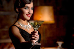 Vamp lady with red lips in restaurant. Wealth concept. Rich vamp lady with red lips giving glass of alcohol cocktail to camera. Happy lady smiling for camera in Royalty Free Stock Images