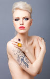 Vamp looking blonde woman with tattoo studio and red lips isolat Royalty Free Stock Photo