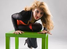 Vamp woman. With a flying hair sitting in aggressive pose on a green chair Stock Photos