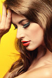 Vamp woman. Close-up portrait of a sensual young woman with red lips over yellow background. Beauty, fashion. Cosmetics, make-up Stock Photo