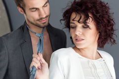 Vamp woman provoke young man. Attractive vamp women provoke young men dragging his tie Royalty Free Stock Image