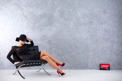 Vamp woman waiting for her next victim. Sexy woman in a black dress and a hat with a brim, sitting on a leather lounge chair, with her envelope bag beside a Royalty Free Stock Image