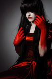 Vamp woman. Young mysterious fashion witch vampire with black hairs against the dark background Royalty Free Stock Photo