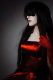 Vamp woman. Young mysterious fashion witch vampire with black hairs against the dark background Stock Photo