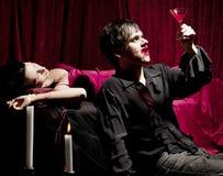 Vampier die van een bloedige drank geniet royalty-vrije stock afbeeldingen