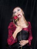 Vampir-Mädchen mit Rose auf schwarzem Hintergrund Lizenzfreie Stockfotos