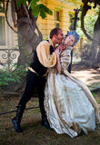 Vampire attacking medieval woman. Male vampire biting women's neck, both dressed in medieval costumes Stock Photo