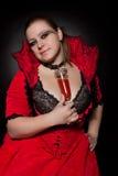 Vampire avec de verre complètement du sang Photographie stock