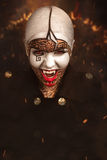 Vampire. Beautiful woman with conceptual art makeup, big white picture on face, red lips, black lines of maze puzzle, close up new portrait. Photo with big dark Royalty Free Stock Image