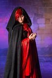 Vampire beauty. Gorgeous young vampire woman standing in a smokey medieval castle Royalty Free Stock Images